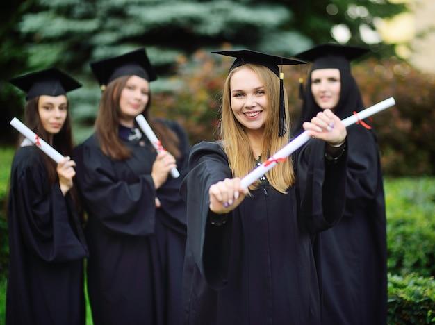 Симпатичная молодая девушка - аспирантка колледжа в черном халате улыбается, держа в руках диплом на фоне группы выпускников.