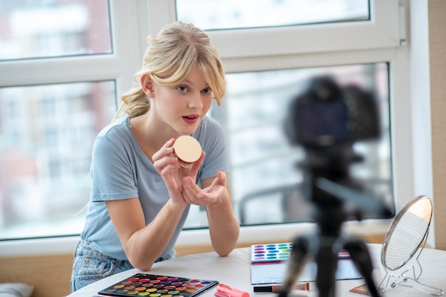 Симпатичная молодая девушка делает онлайн-урок по макияжу