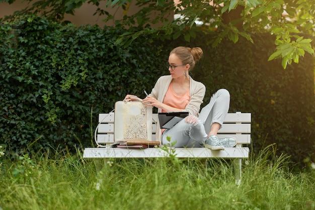 Симпатичная молодая девушка сидит на белой скамейке в зеленом парке. на ней синие джинсы, легкая футболка и кардиган.