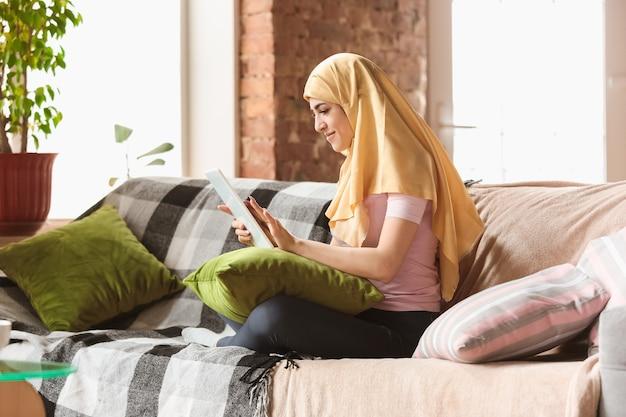 검역과 자가 격리 기간 동안 집에 있는 꽤 젊은 이슬람 여성