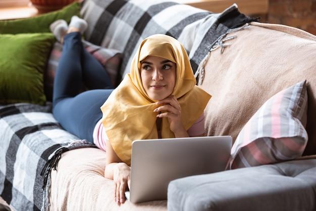 Симпатичная молодая мусульманка дома во время карантина и самоизоляции