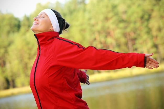 自然な緑の背景の上に自由な時間を楽しんでいるかなり若い女性
