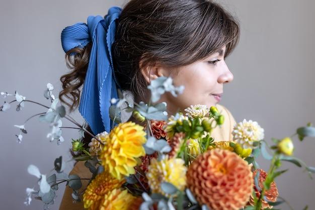 예쁜 젊은 여성이 국화 꽃다발을 들고 있습니다.