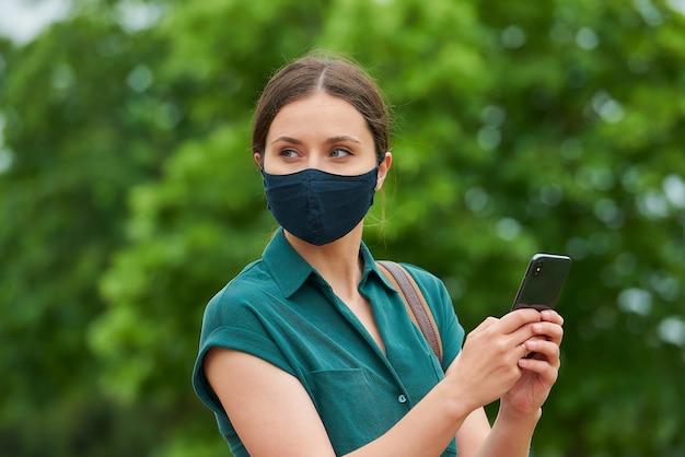 의료 얼굴 마스크에 꽤 젊은 여자는 공원에서 산책하는 동안 스마트 폰을 들고있다