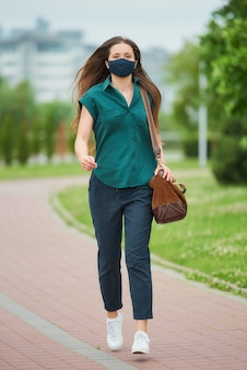 네이비 블루 의료 얼굴 마스크에서 꽤 젊은 여자는 공원에서 가죽 가방을 들고 점프