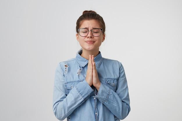Симпатичная молодая женщина в очках стоит с закрытыми глазами, сложив руки перед собой, молящийся жест