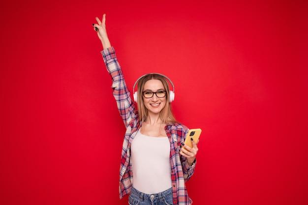 Симпатичная молодая женщина в стильной одежде слушает музыку в наушниках со своего телефона на красном фоне
