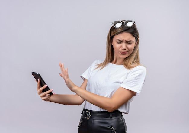 Симпатичная молодая женщина в белой футболке в солнечных очках на голове выражает негатив, держа мобильный телефон на белой стене