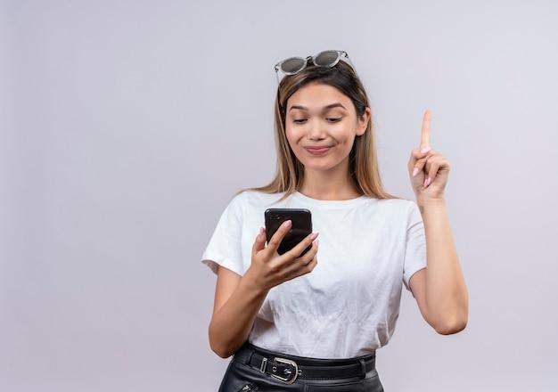 Симпатичная молодая женщина в белой футболке в солнечных очках на голове показывает указательным пальцем и смотрит на мобильный телефон на белой стене