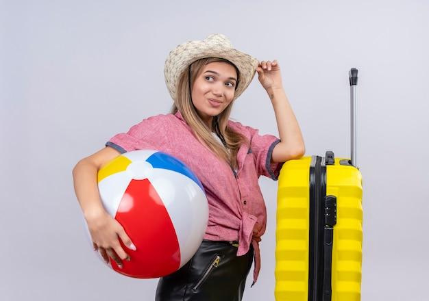 Симпатичная молодая женщина в красной рубашке и шляпе от солнца держит надувной мяч и кладет руку на желтый чемодан на белой стене