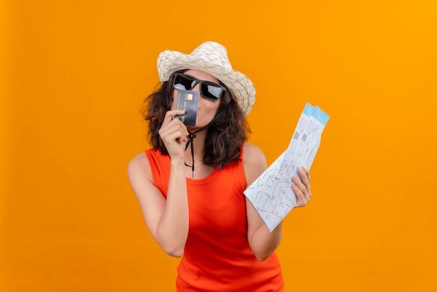 日よけ帽とサングラスを身に着けているオレンジ色のシャツを着た短い髪のかなり若い女性がクレジットカードにキスする地図と飛行機のチケットを持っています