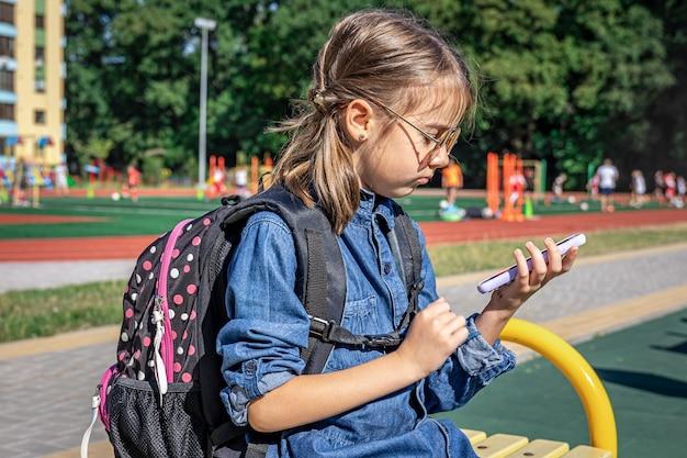 Ученица начальной школы с рюкзаком использует смартфон, сидя возле школы.