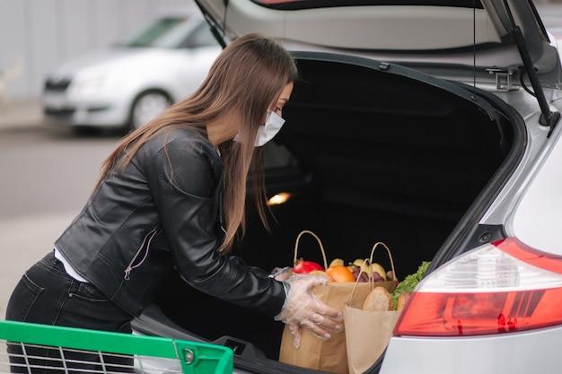 트롤리에서 자동차로 슈퍼마켓에서 식료품을 가져가는 젊은 매력적인 여성의 과정