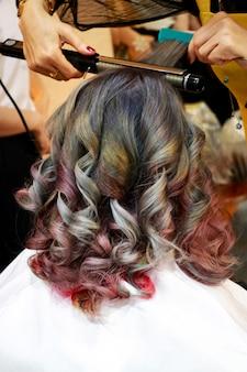 プロの美容師がサロンでスパイラルになるように多色の髪にアイロンをかけています