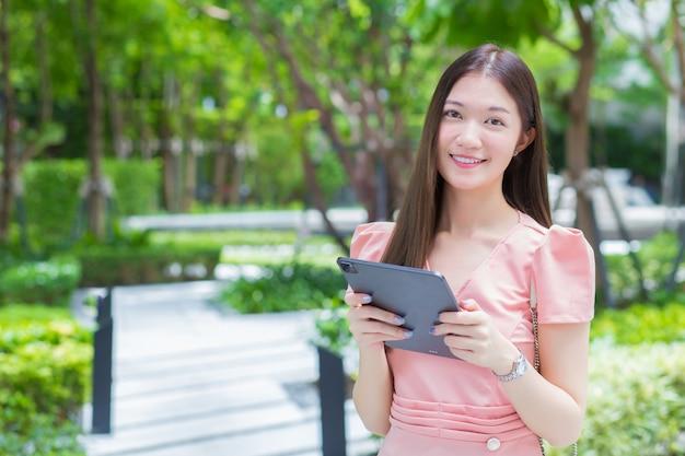 긴 머리를 가진 한 전문 아시아 여성 사업가가 손에 든 태블릿을 보면서 정원에서 웃고 있으며, 어디에서나 일하고 있습니다.