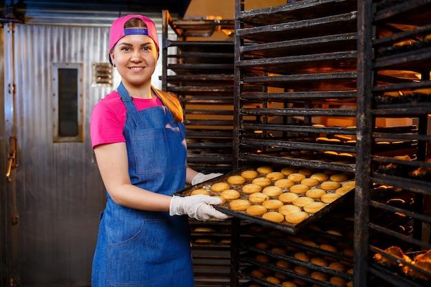 전문 제빵사 소녀가 손에 신선한 쿠키가 든 쟁반을 들고 있습니다. 빵집에서 달콤한 패스트리
