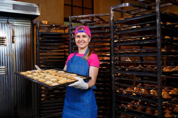 Девушка-профессиональный пекарь держит в руках поднос со свежим печеньем. сладкая выпечка в пекарне