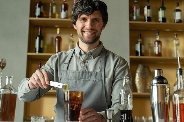 Профессиональный бармен украшает коктейль лаймом, бармен готовит коктейль с виски и колой, готовит коктейли в баре.