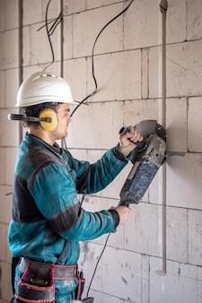 Профессиональный строитель в спецодежде работает с режущим инструментом.
