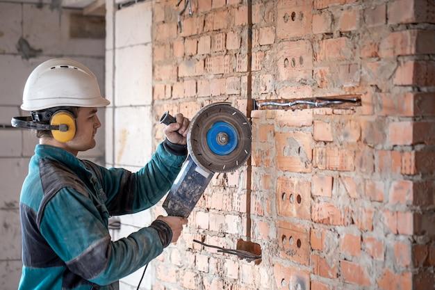 作業服のプロのビルダーは、切削工具を使用します。