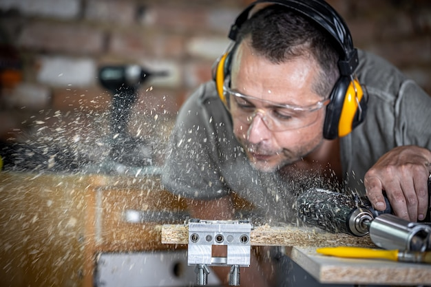 Профессиональный плотник в процессе сверления дерева сдувает остатки древесины.