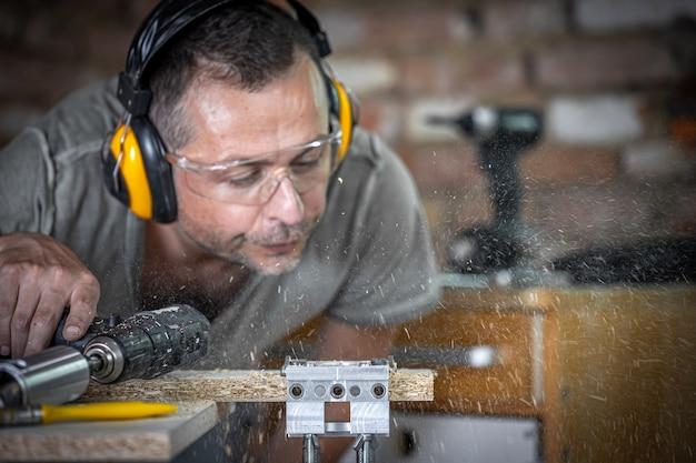 木材を掘削する過程でプロの大工が残りの木材を吹き飛ばします。