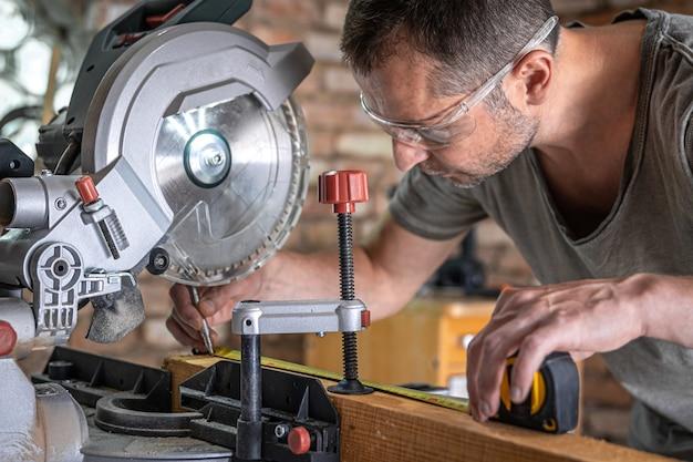 プロの大工がワークショップで丸鋸マイターソーを使って作業します。