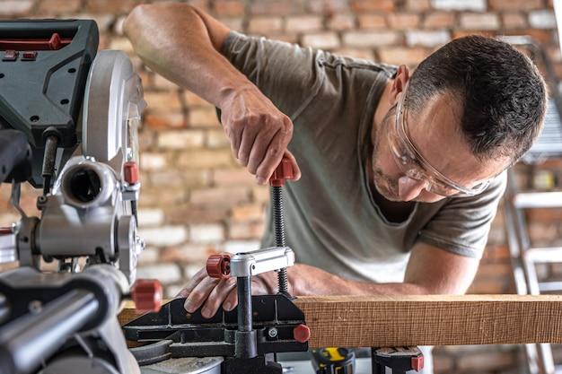 전문 목수가 작업장에서 원형 톱 연귀톱으로 작업합니다.