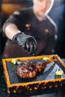 전문 셰프가 버터와 조미료를 곁들인 육즙 가득한 그릴 스테이크를 아름답게 선보입니다. 레스토랑에서 구운 고기입니다.