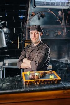 Профессиональный повар красиво подает сочный стейк на гриле с маслом и приправами.