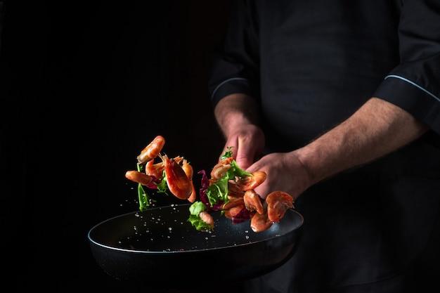 전문 요리사가 야채와 함께 팬에 새우를 요리합니다. 어두운 배경에서 해산물, 건강한 채식주의 음식, 음식을 요리하세요. 움직임이 멈춥니다. 무료 광고 공간
