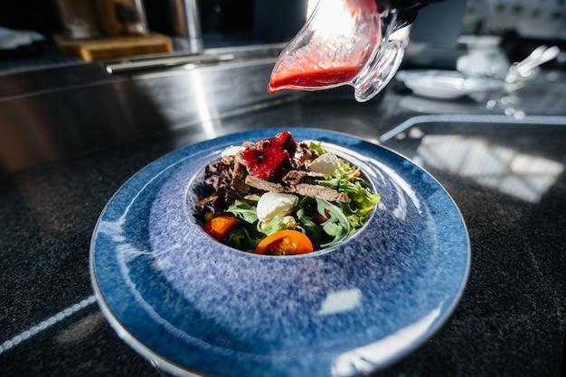 プロのシェフがモダンでスタイリッシュなレストランで、緑の野菜とジューシーな子牛肉のおいしい新鮮なサラダを用意しています。レストランでの料理。