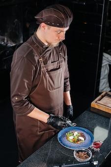 Профессиональный повар готовит вкусный свежий салат из зеленых овощей и сочной телятины в современном стильном ресторане. готовим в ресторане.