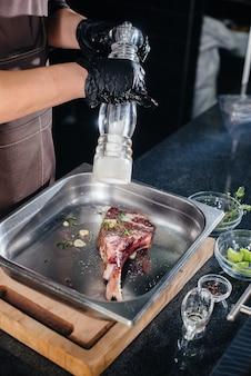 전문 셰프가 신선한 고기로 육즙이 풍부한 스테이크를 소금에 절입니다. 미식가 레스토랑의 mca에서 요리.