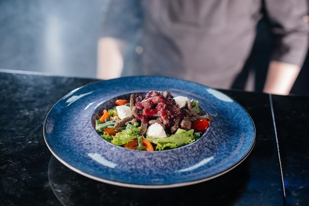 Профессиональный повар подает свежеприготовленный салат из помидоров и телятины с соусом в ресторане изысканной кухни крупным планом.
