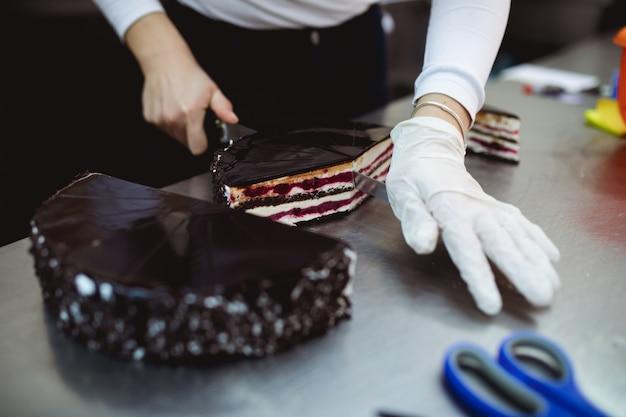 プロの菓子職人がケーキを切る。