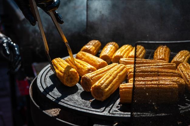 전문 요리사가 그릴 야외, 음식 또는 케이터링 컨셉에서 옥수수를 준비합니다.