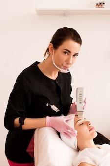 Профессиональный косметолог делает ультразвуковую чистку лица.