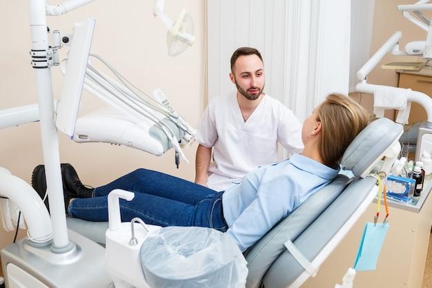 プロの歯科医が女性患者とコミュニケーションを取ります。患者診察のための歯科医院。歯科治療プロセスの議論。