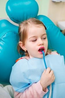 子供の歯科医である専門医は、小さな女の子の歯を器具で治療します。患者診察のための歯科医院。子供の歯科治療のプロセス