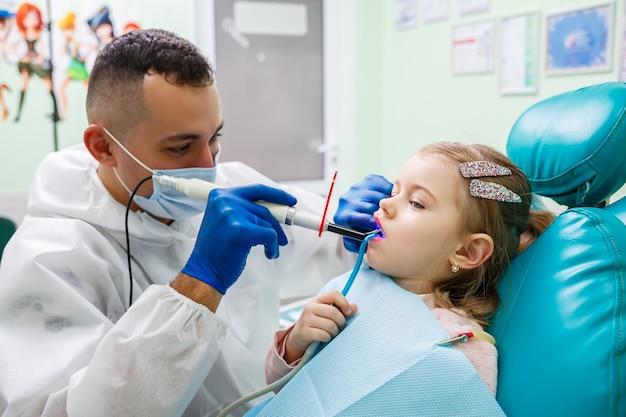 Профессиональный врач, детский стоматолог, лечит зубки маленькой девочки инструментами. стоматологический кабинет для обследования пациентов. процесс лечения зубов у ребенка