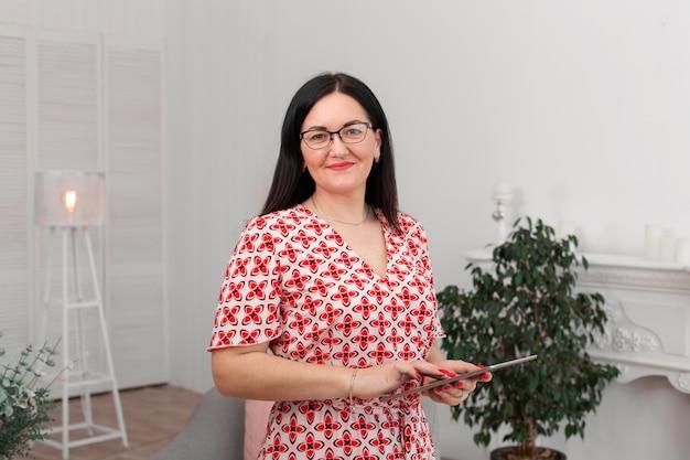 眼鏡をかけた専門の医師心理学者は、明るいオフィスに座ってタブレットを手に持ち、カメラに微笑んでいます。心理療法。女性心理療法士