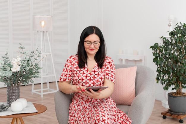 眼鏡をかけた専門の医師心理学者は、彼の手でタブレットとカメラに笑顔で明るいオフィスに座っています
