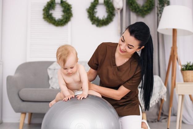 医療室でフィットネスボールでエクササイズをして幸せな赤ちゃんとプロの女性マッサージ師。医療と医療のコンセプト。