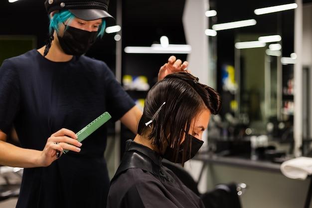 전문 소녀 미용사가 고객 이발을 만듭니다. 소녀는 미용실에서 마스크에 앉아있다.