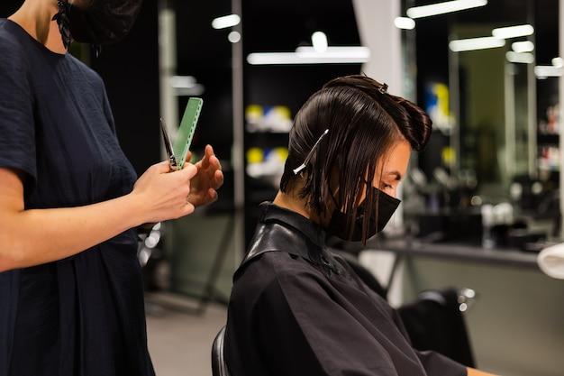 プロの女の子の美容師がクライアントのヘアカットを行います。女の子は美容院でマスクに座っています