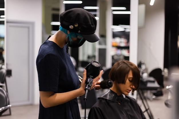 プロの女の子の美容師がクライアントのヘアカットを行います。女の子は美容院でマスクに座っています 無料写真