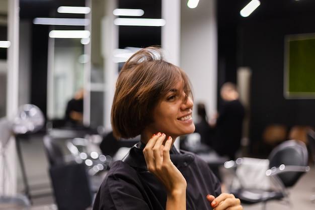 Профессиональный парикмахер делает клиентскую стрижку. девушка сидит в маске в салоне красоты