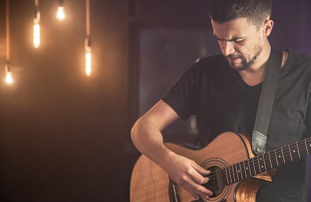 검은 티셔츠를 입은 전문 기타리스트가 콘서트에서 전구와 어쿠스틱 기타를 연주합니다.