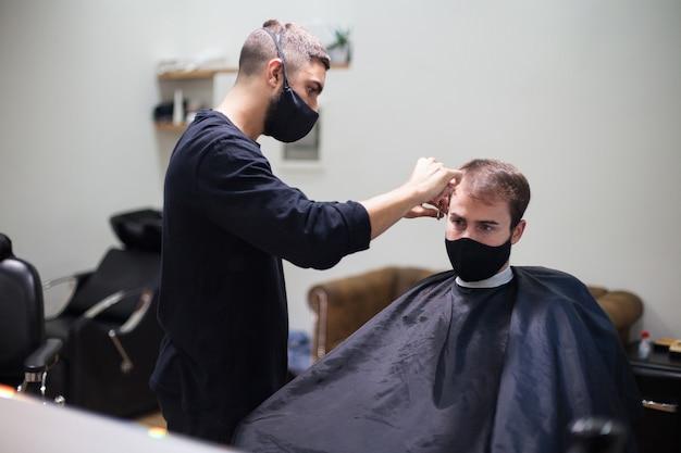 コロナウイルス中にクライアントに髪を切る保護マスクを身に着けているプロの美容師